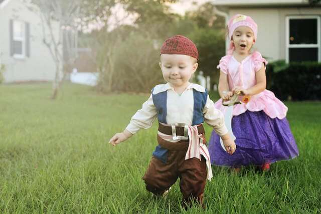 Brother and sister in pirate costumes run through yard.