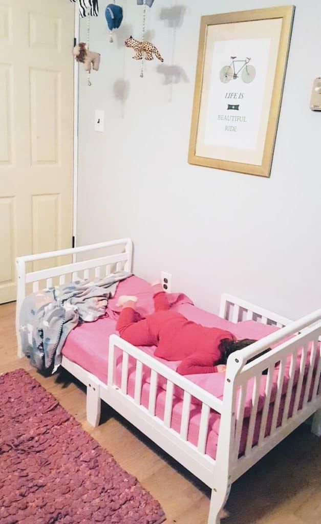 Toddler girl sleeps in big girl bed.