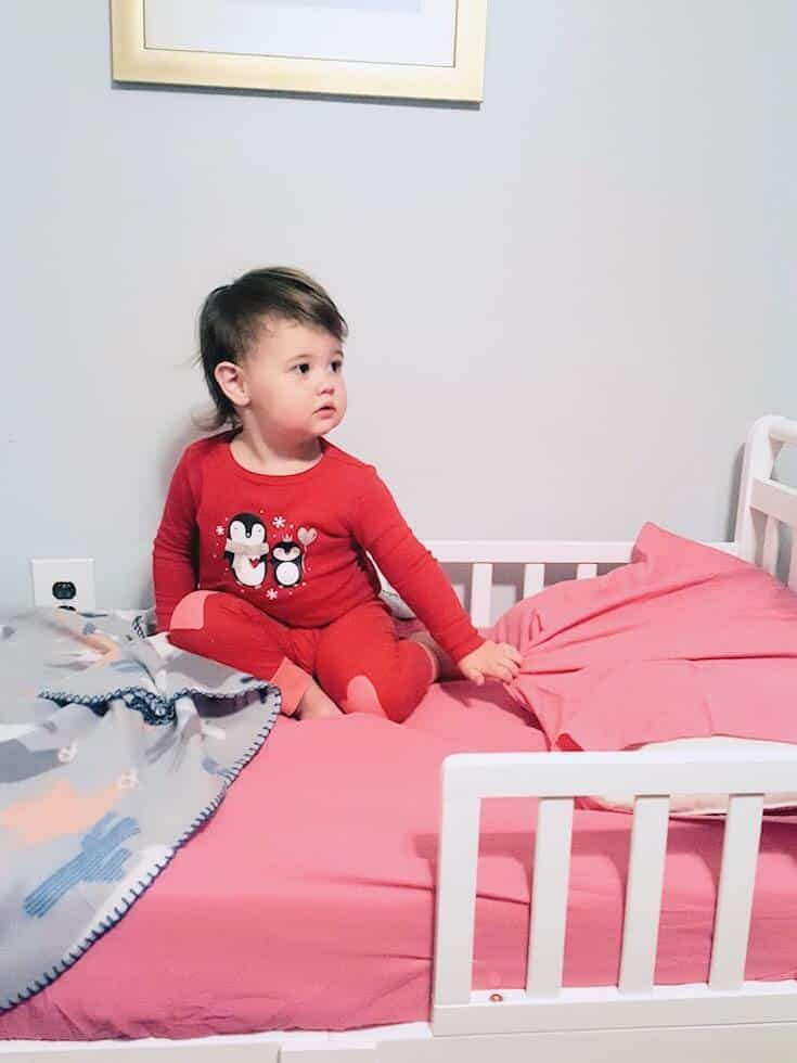 Toddler girl sits on her bed.
