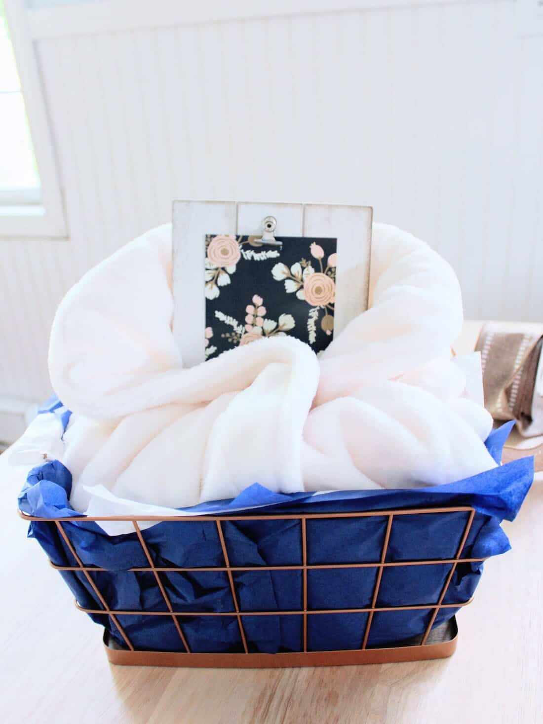 New mom gift basket with blue tissue paper.