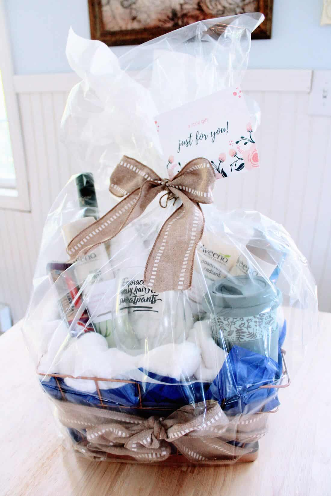 Gift basket for moms wrapped in clear paper.
