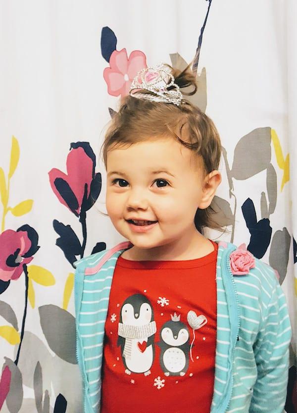 Toddler girl smiles at camera while wearing mini tiara.