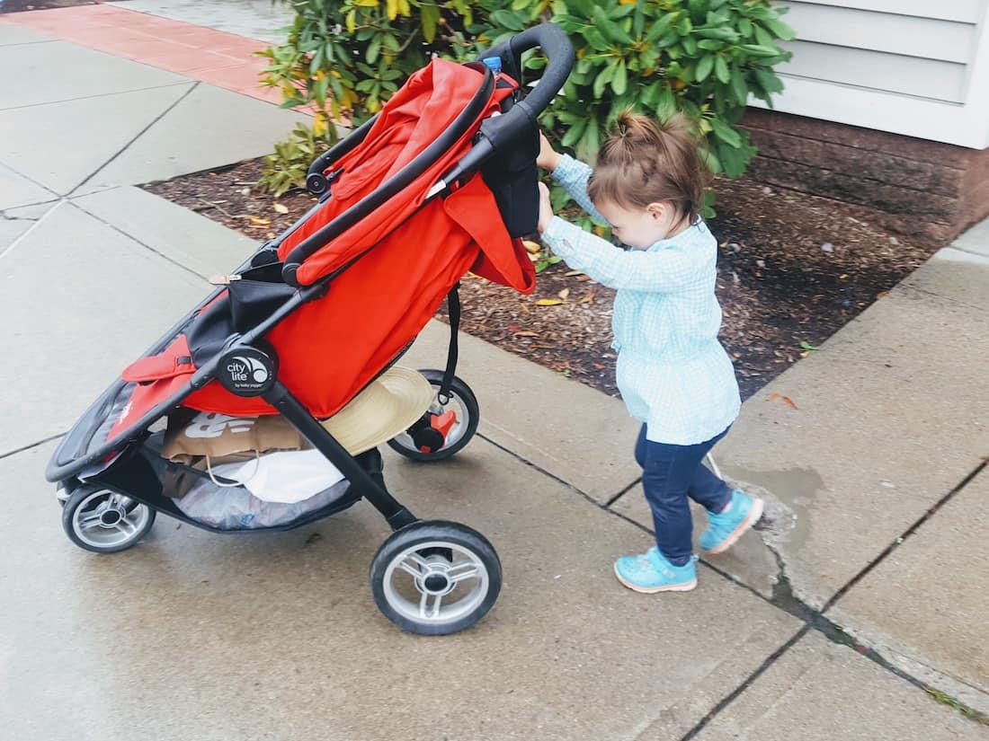 Toddler girl pushes stroller down sidewalk.