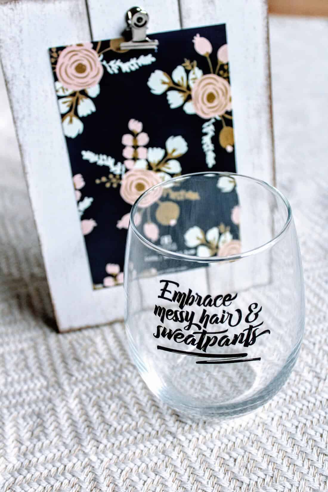 Embrace messy hair and sweatpants wine glass next to picture frame for gift basket.