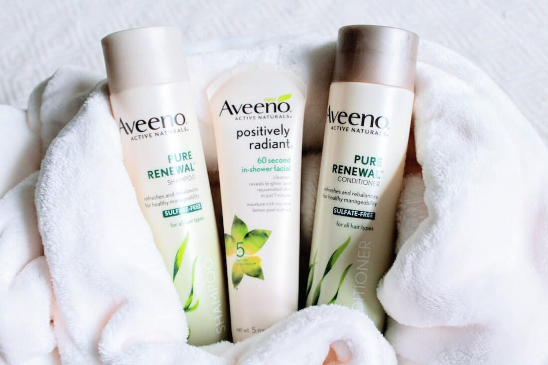 Aveeno skin care products on white towel.