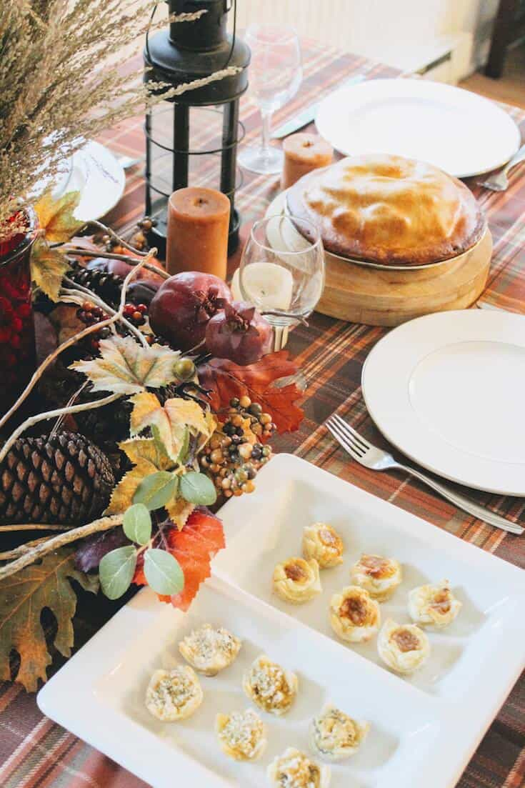White plates on Thanksgiving table with food.
