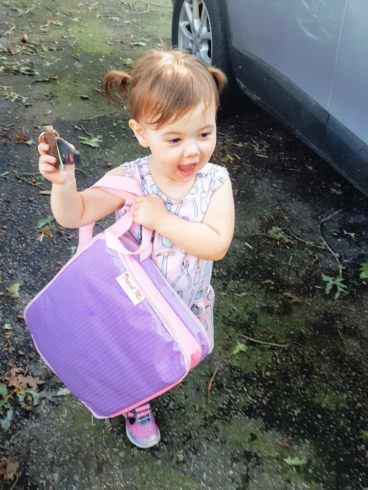 Toddler girl carries entertainment bag for travel.