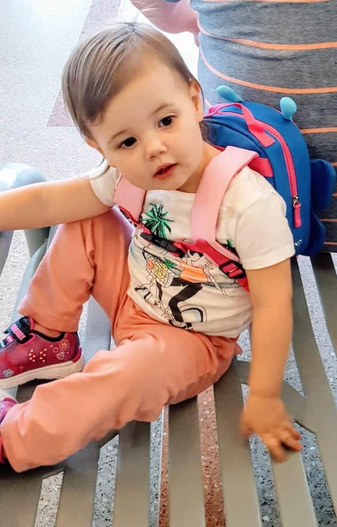 Toddler girl wears backpack for travel.