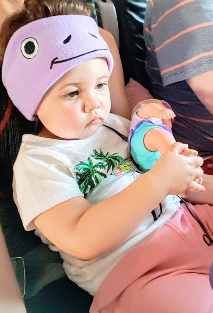 Toddler girl plays with doll on plane trip.