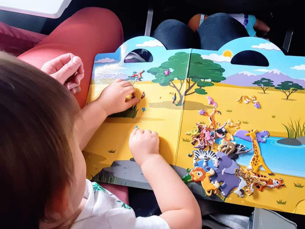 Toddler girl stays entertained on flight with book.