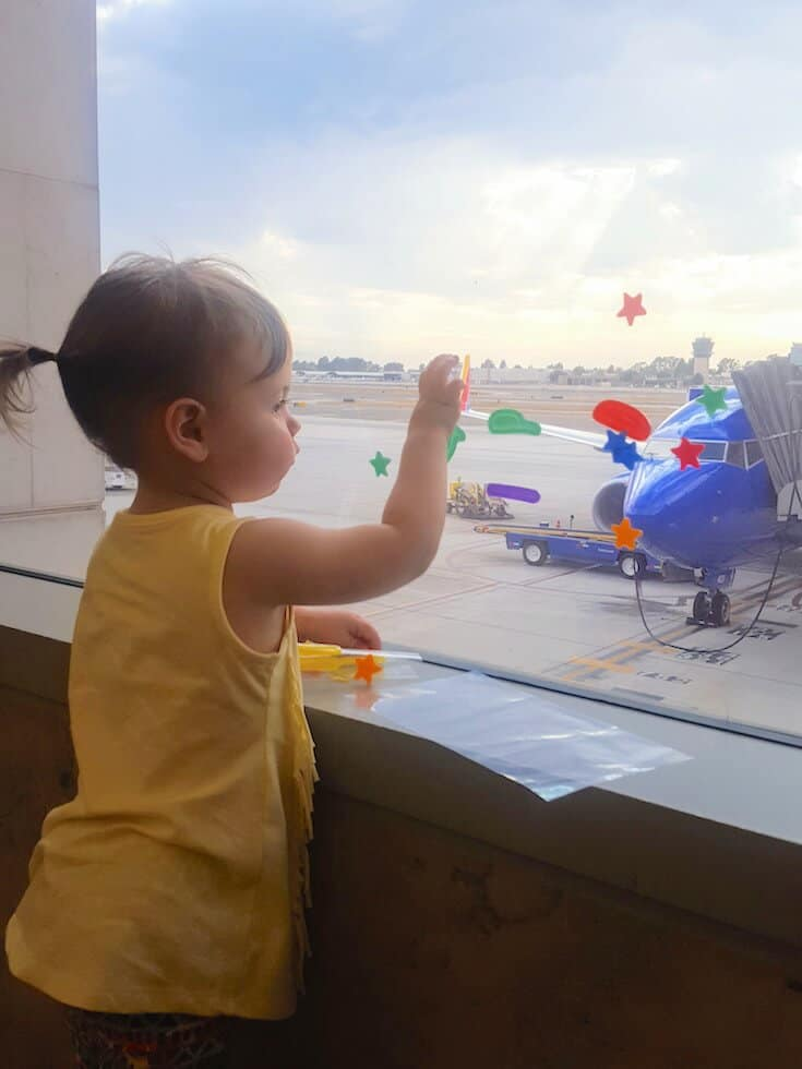 Toddler plays with stickers on airport window.