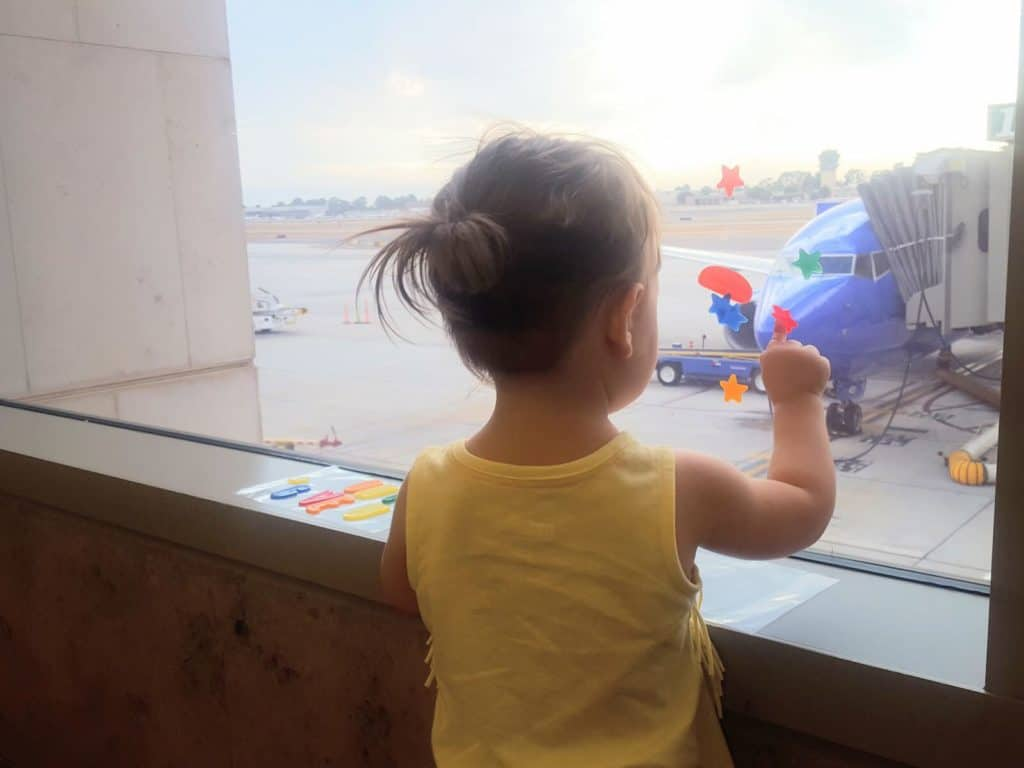 Toddler girl looks at parked plane through airport window.