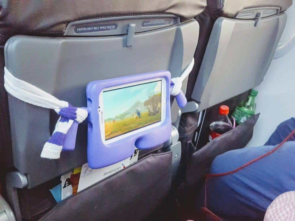 Toddler girl watches iPad on plane.