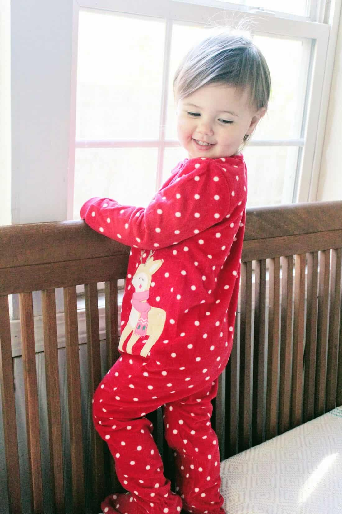 Toddler girl in Christmas pajamas stands in crib.