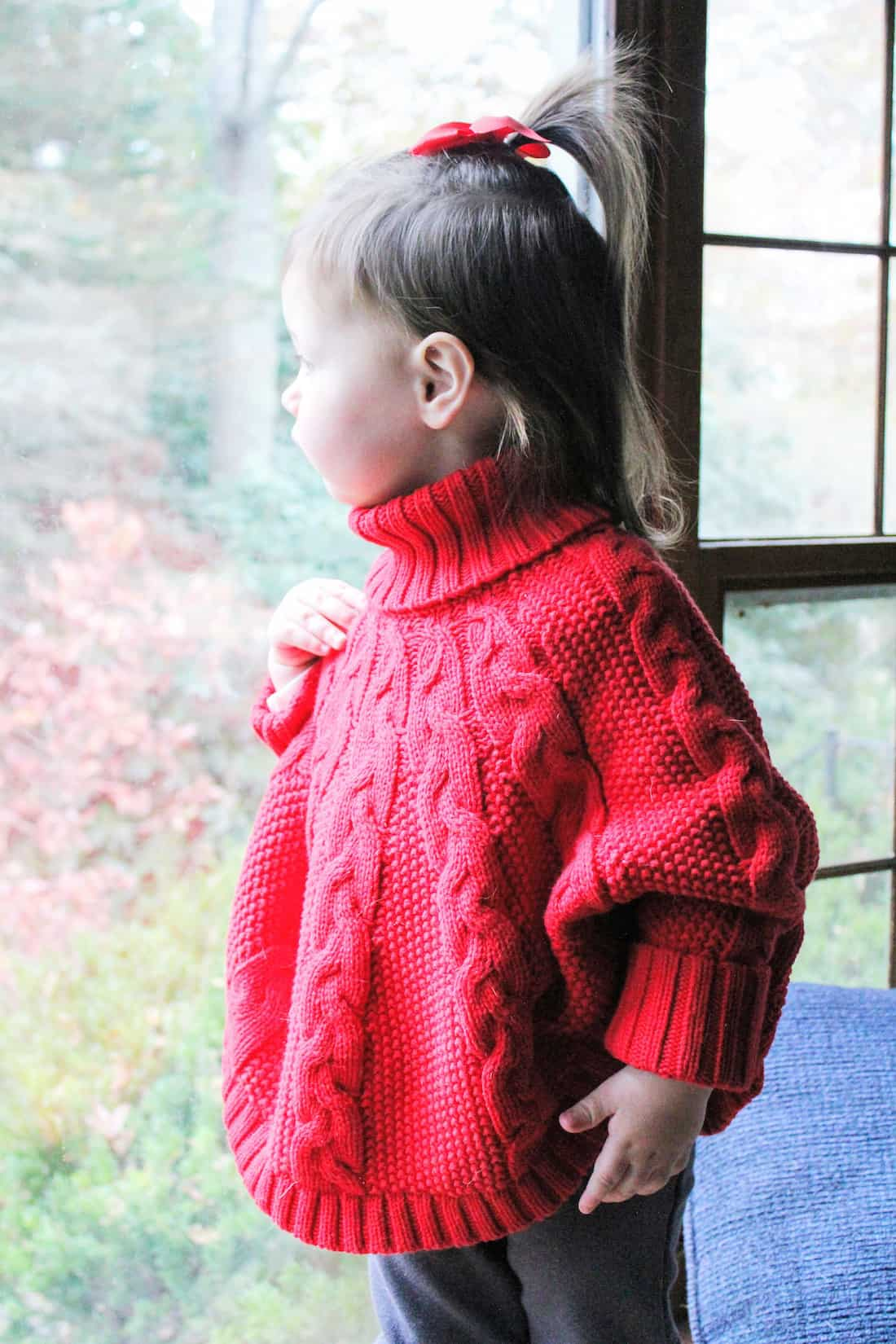 Toddler girl in red holiday sweater looks through window.