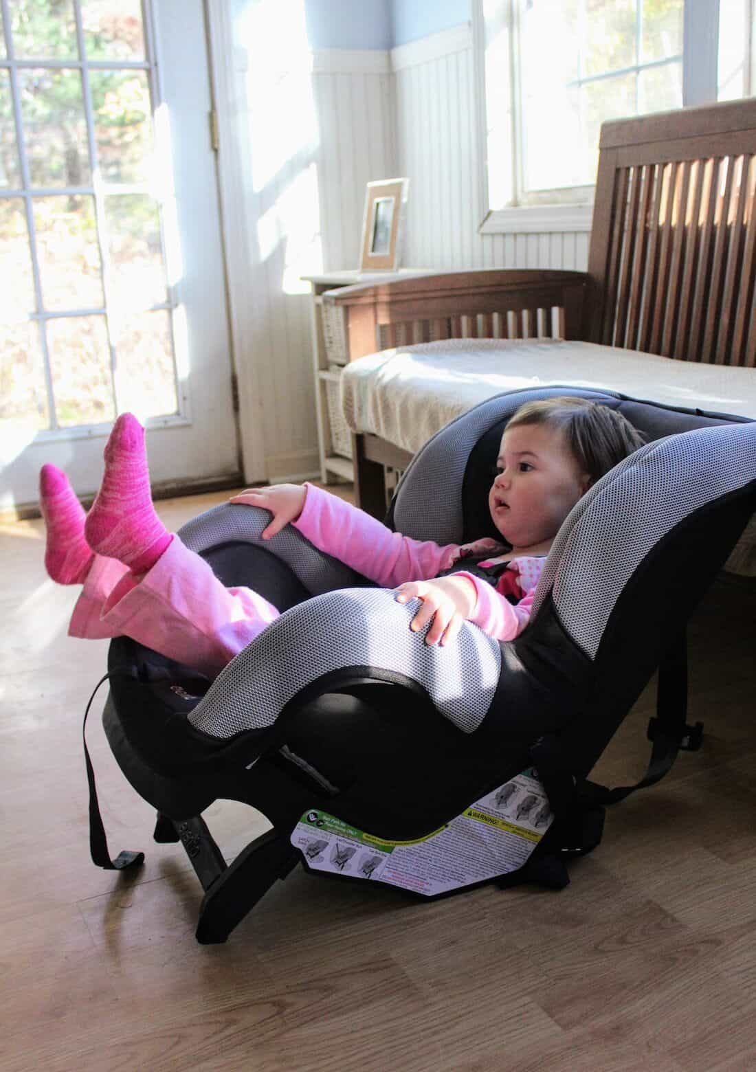 Toddler girl sits in Car Seat inside of house.