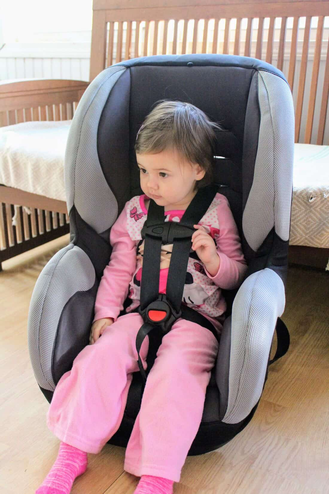 Toddler girl is strapped into carseat.