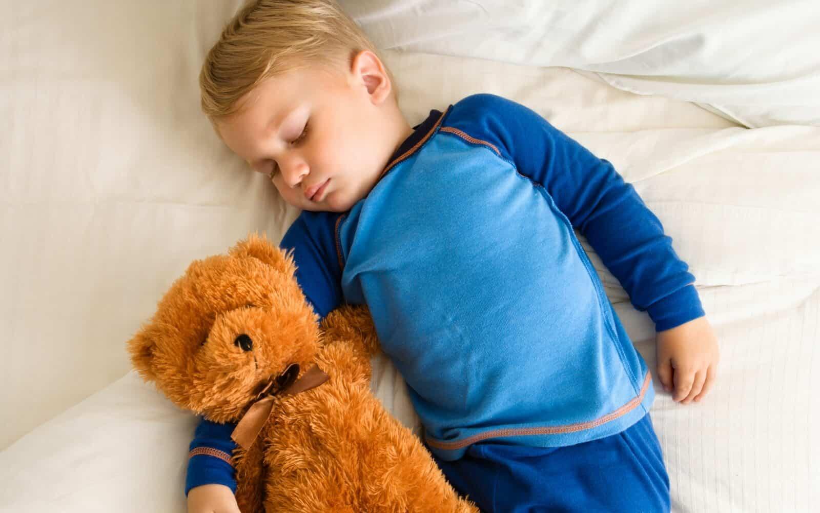 Toddler boy sleeps next to teddy bear.