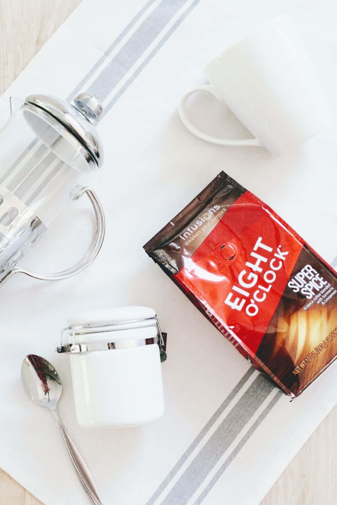 Eight O\'Clock Coffee product next to mug and coffee items.