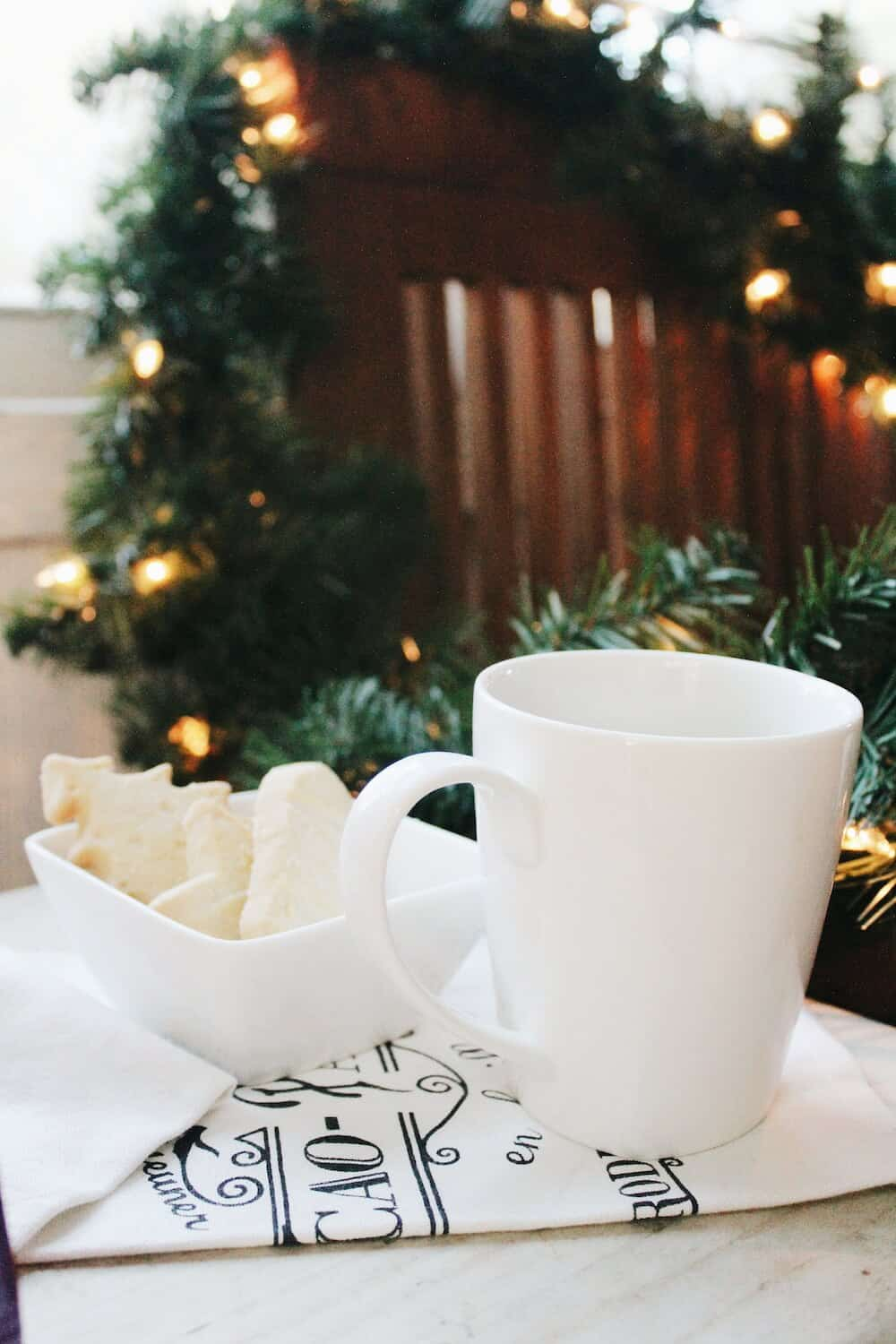 Cookies and mug in front of Christmas decorations.