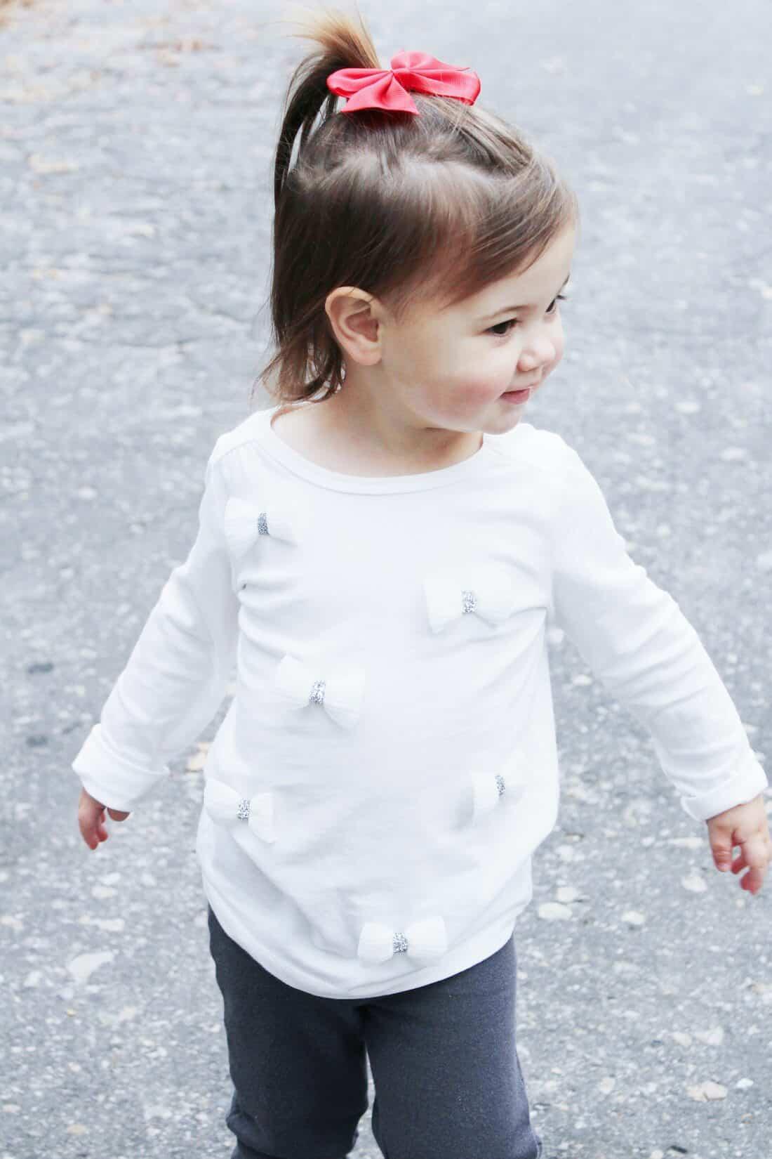 Toddler girl walks down road.