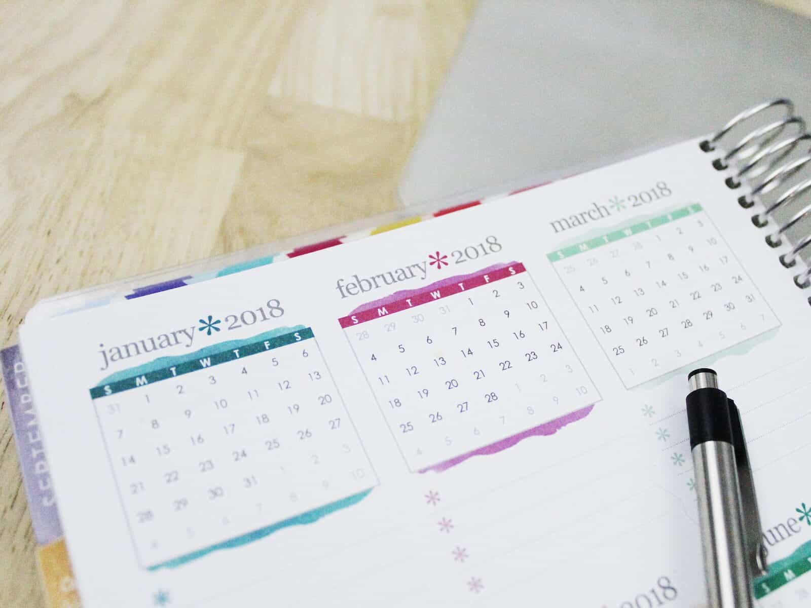 Calendar and pen on wooden table.