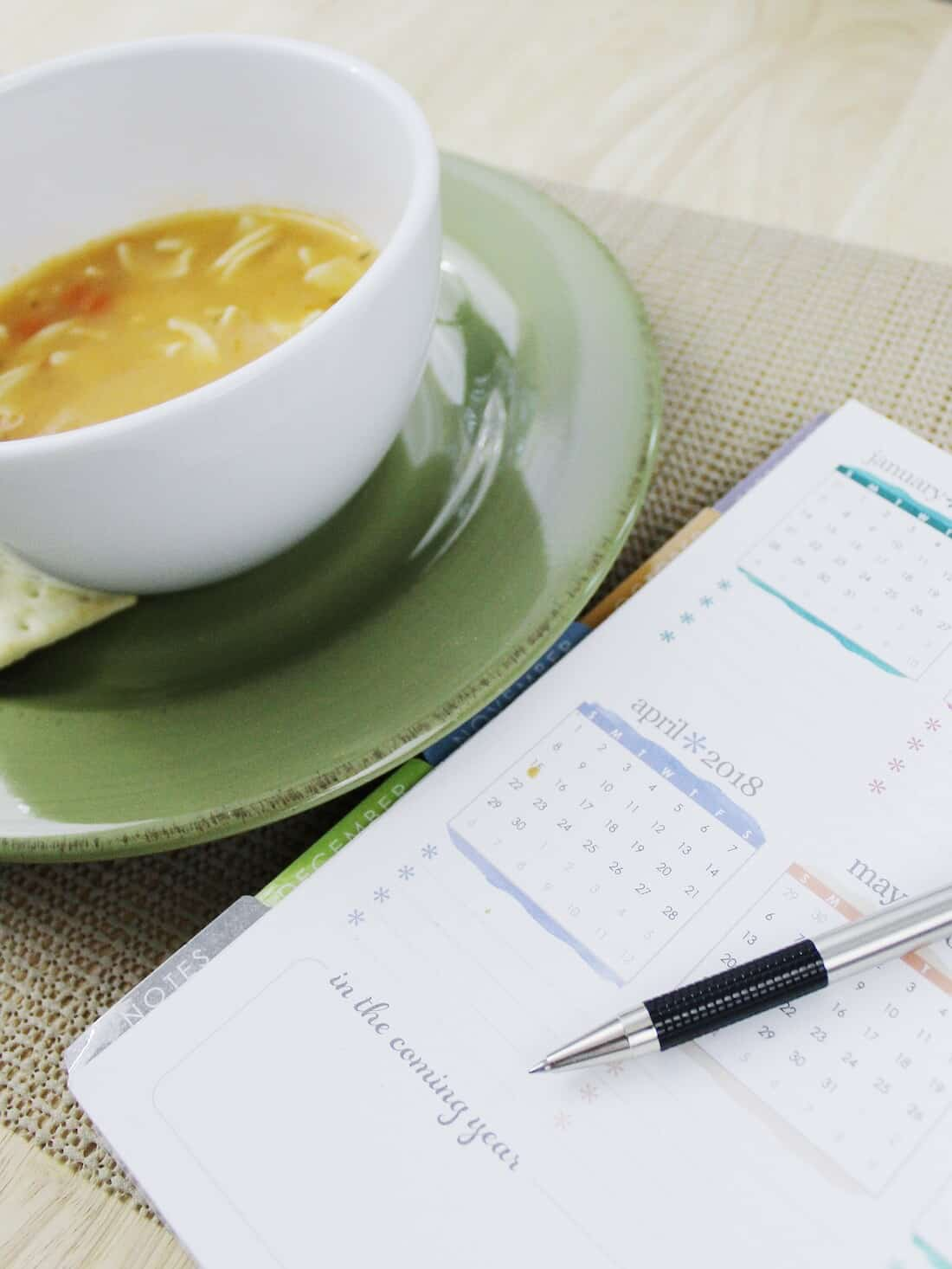 Bowl of soup and planner on kitchen table.