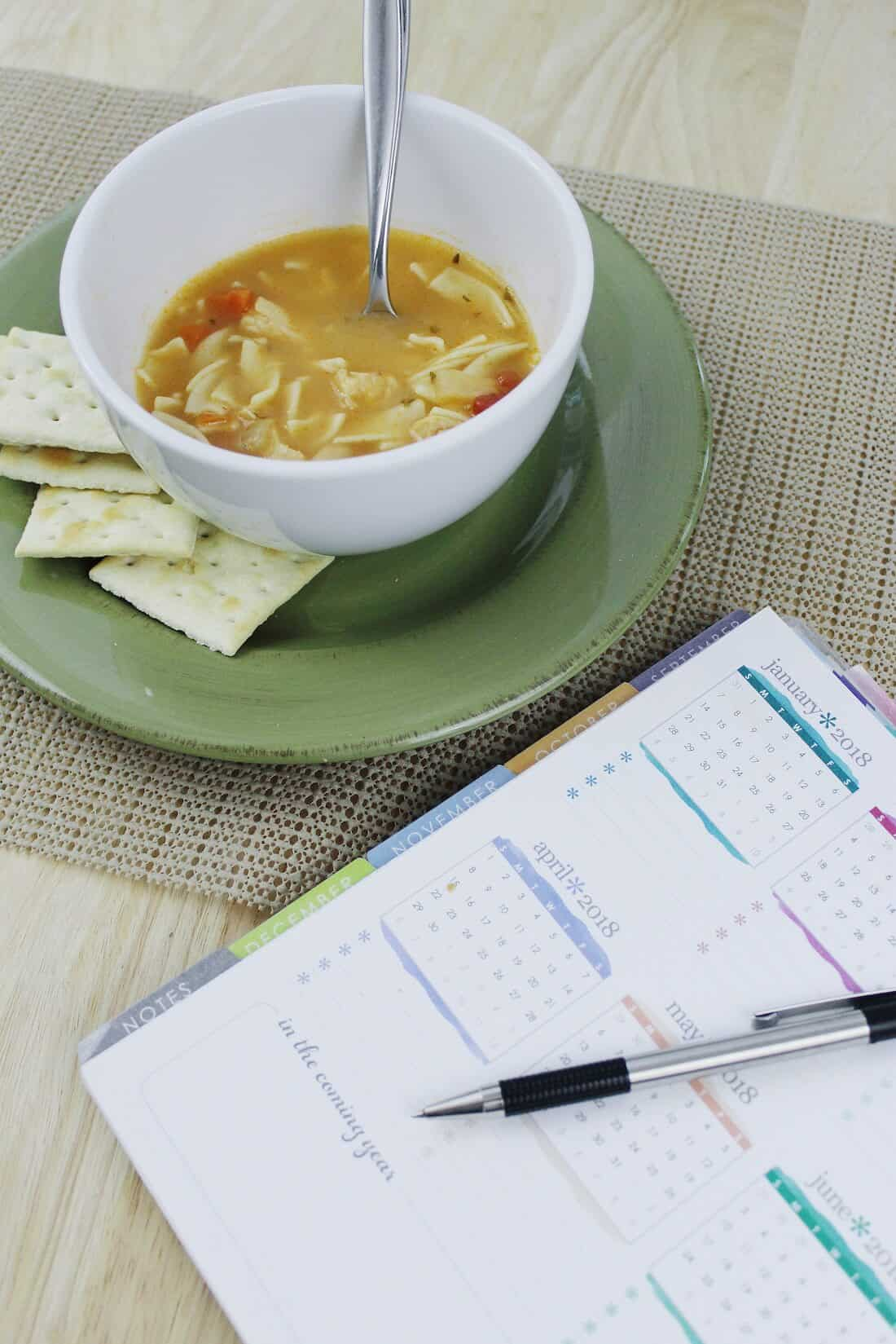 Soup and crackers next to planner and pen.