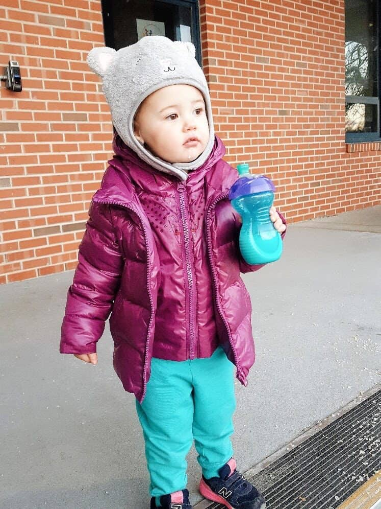 Toddler girl in puffer coat and fuzzy animal hat.