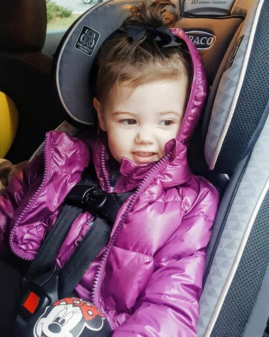 Toddler girl in puffer coat strapped into car seat.