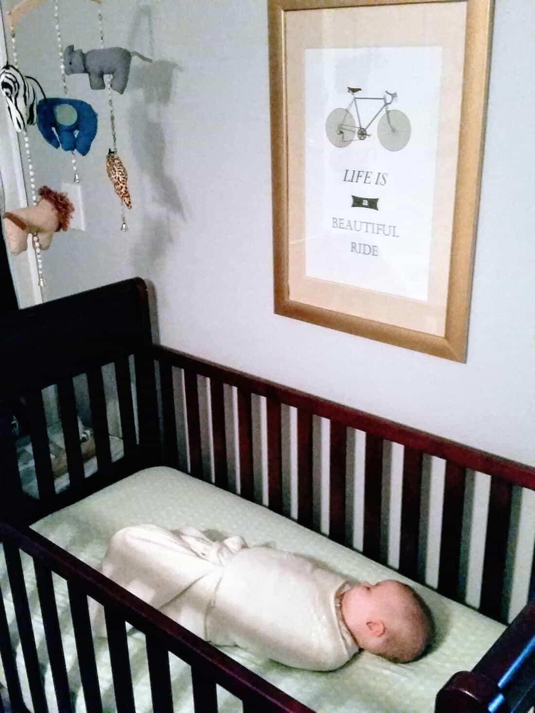Baby girl sleeps in crib with swaddle.