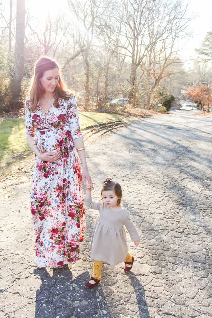Pregnant woman walks down street with daughter.