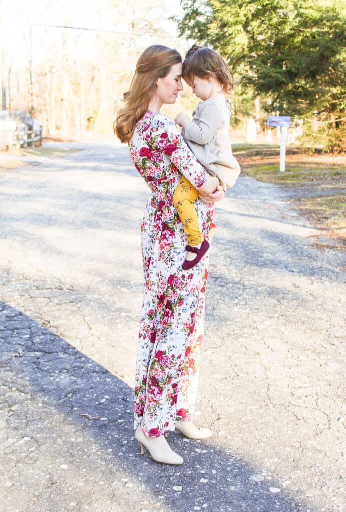Woman holds daughter for pictures during second pregnancy.