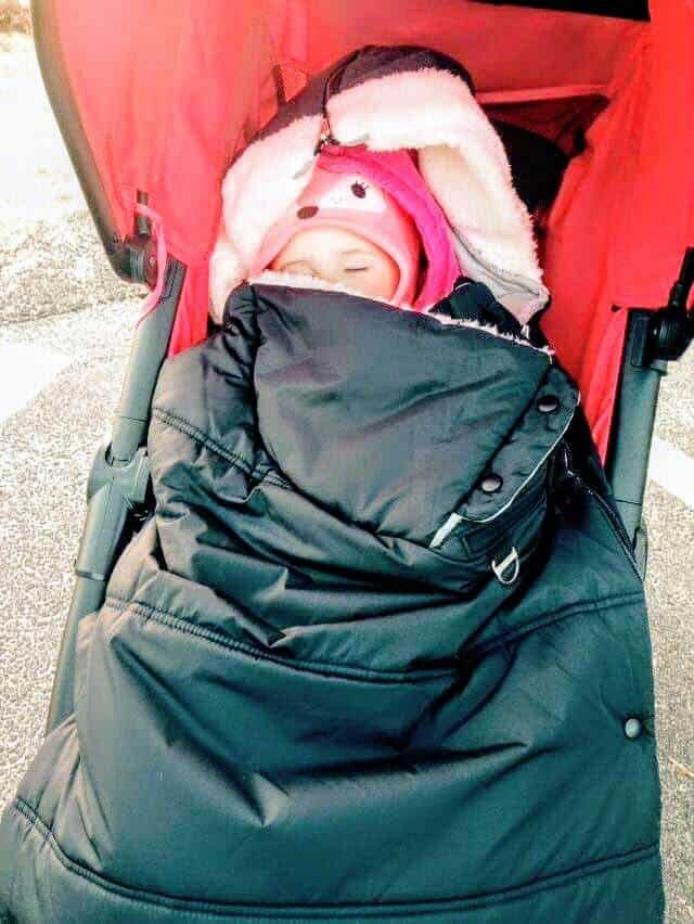 Toddler girl sleeps in warm and cozy stroller.