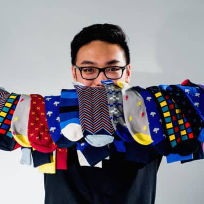 Man holds several socks with various patterns.