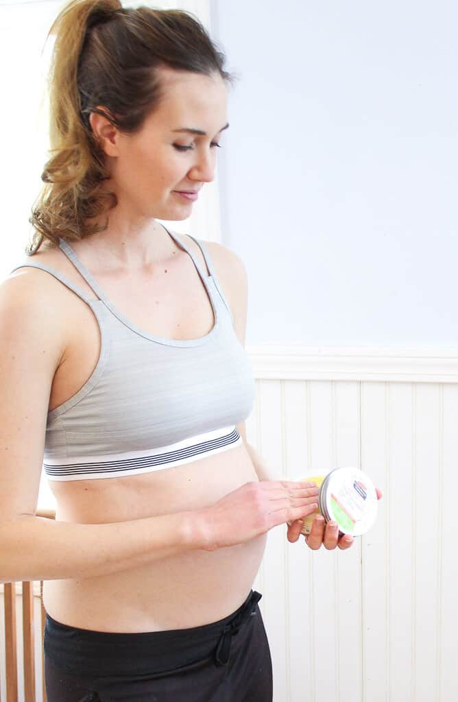 Pregnant woman holds container of stretch mark cream.