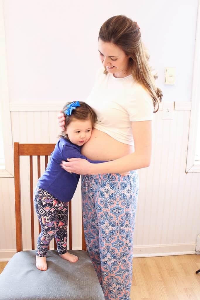 Toddler girl hugs her mother\'s pregnant belly.