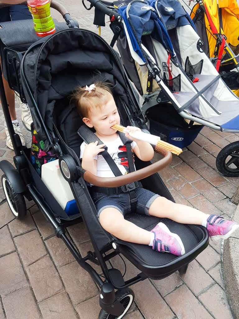 Toddler eats snack in stroller at Disney.