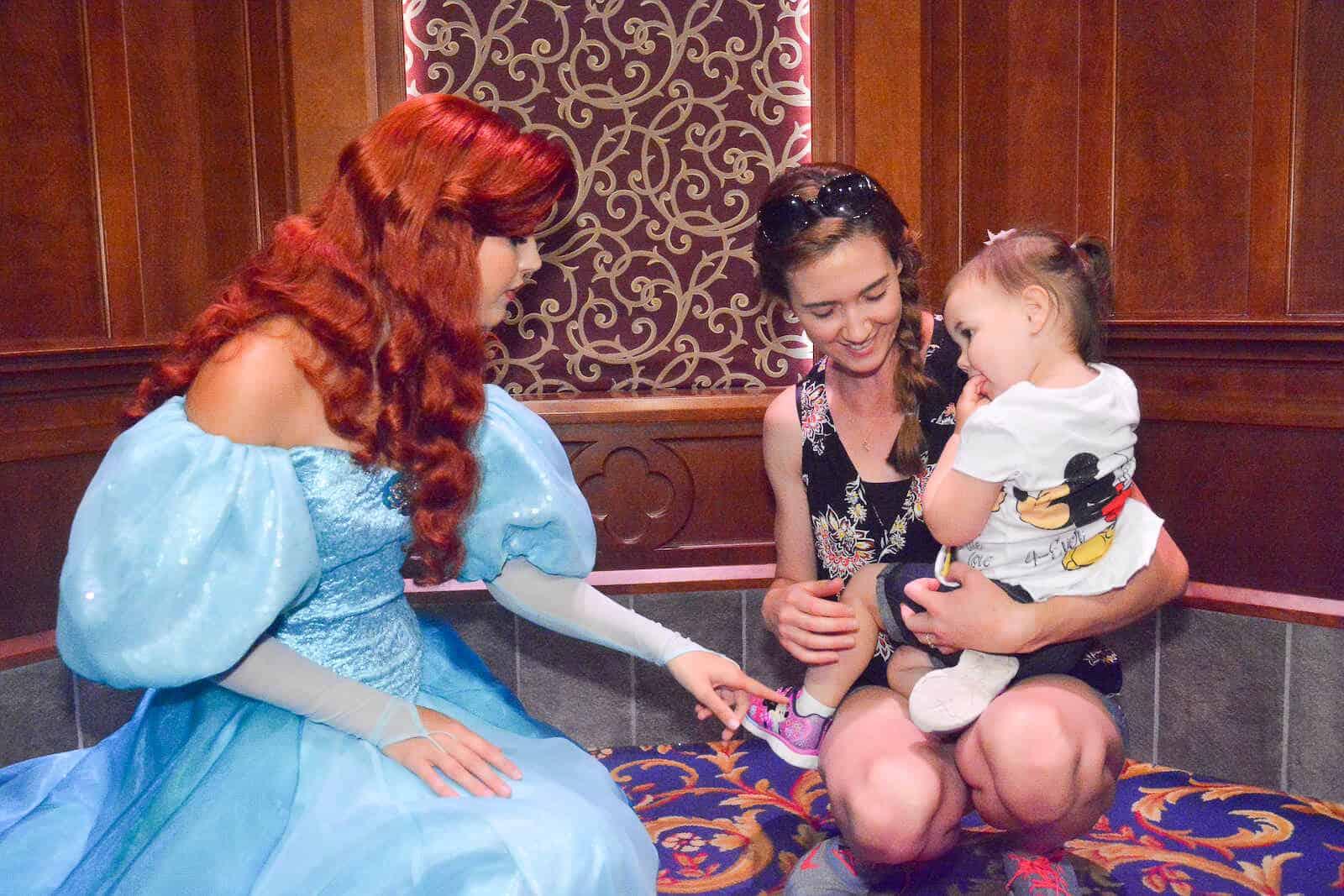 Mother introduces toddler girl to princess at Disney.