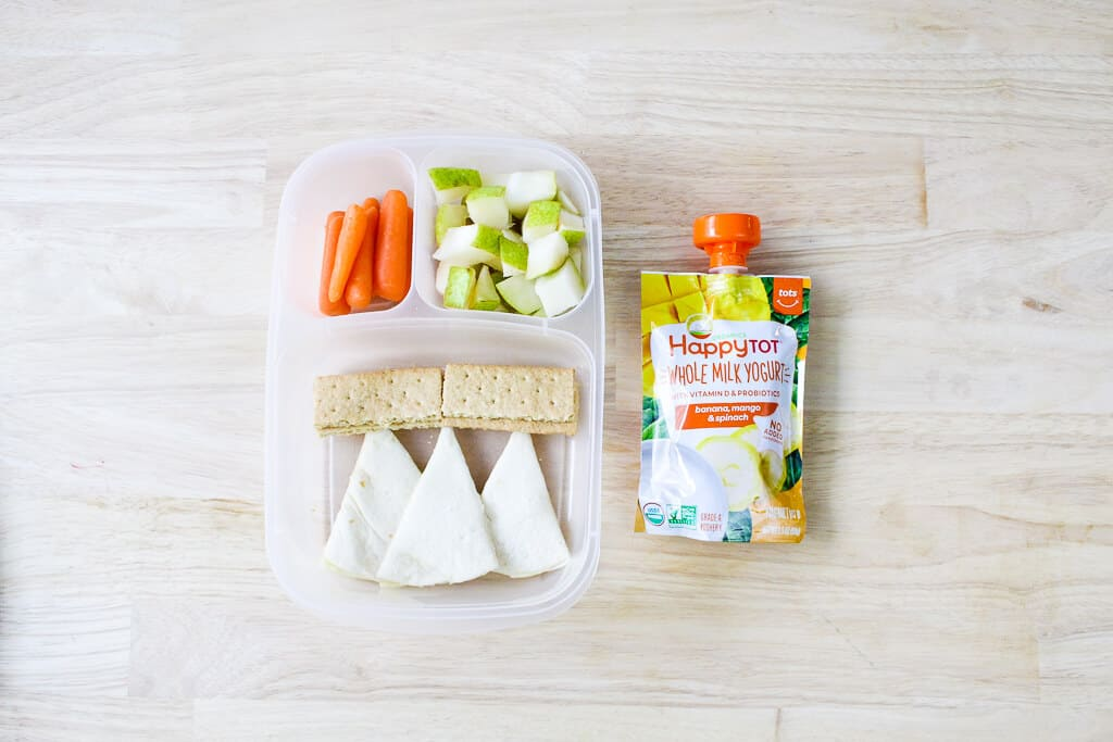 toddler daycare lunch with carrots, pears, quesadilla and graham crackers with yogurt pouch on a table