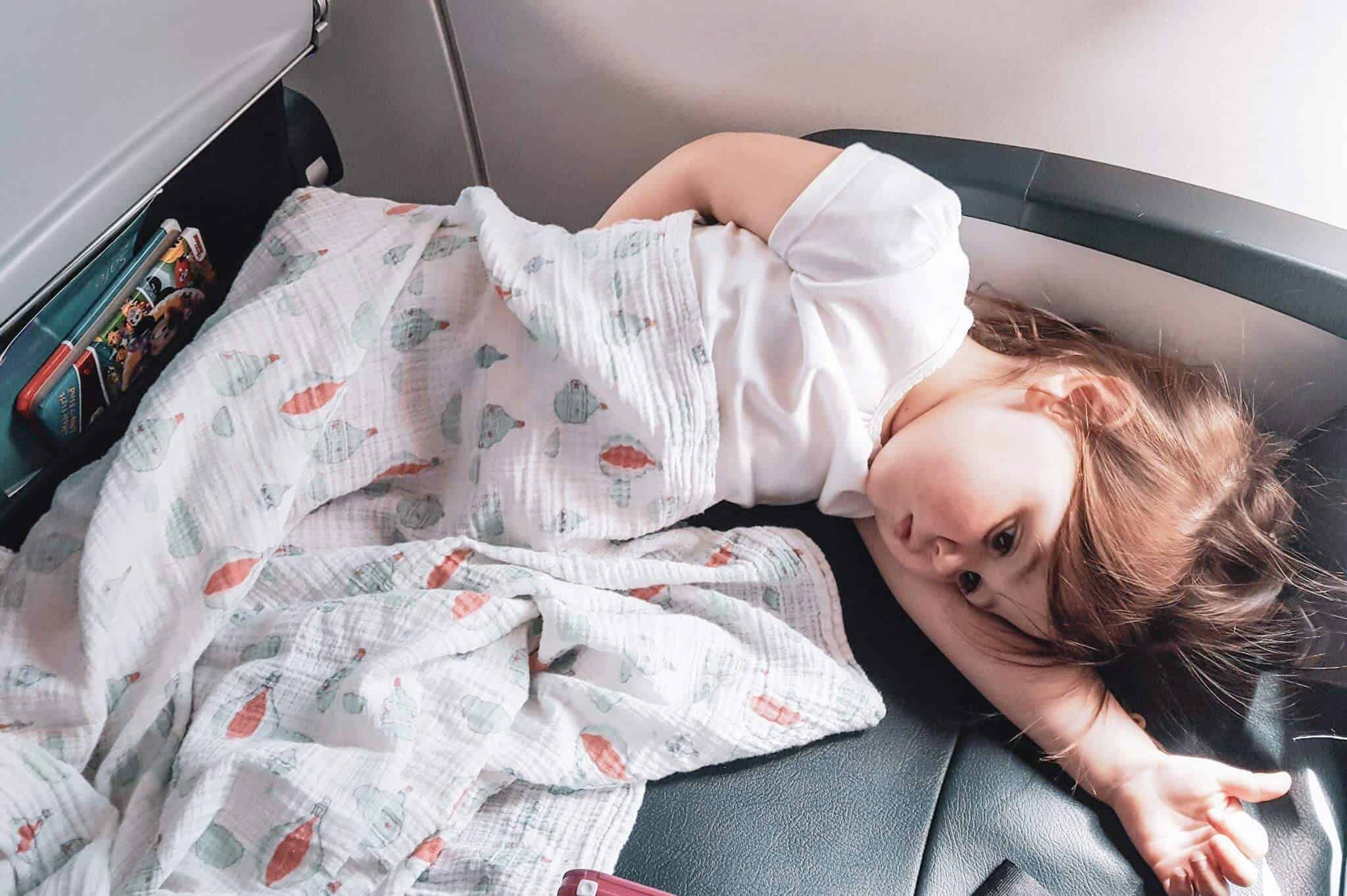 Toddler uses travel gear to sleep on plane.