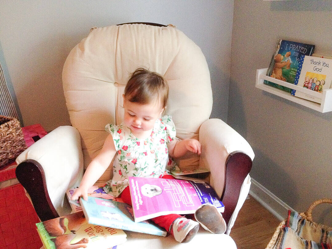 Little girl sits on rocking chair glider with a lap filled with books.
