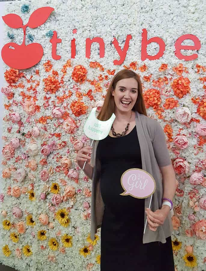 Woman stands in front of step and repeat backdrop at baby show in New York.