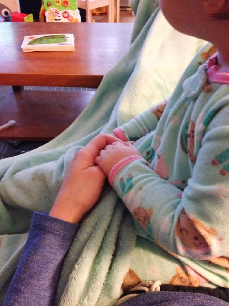 Woman holds baby girl\'s hand.