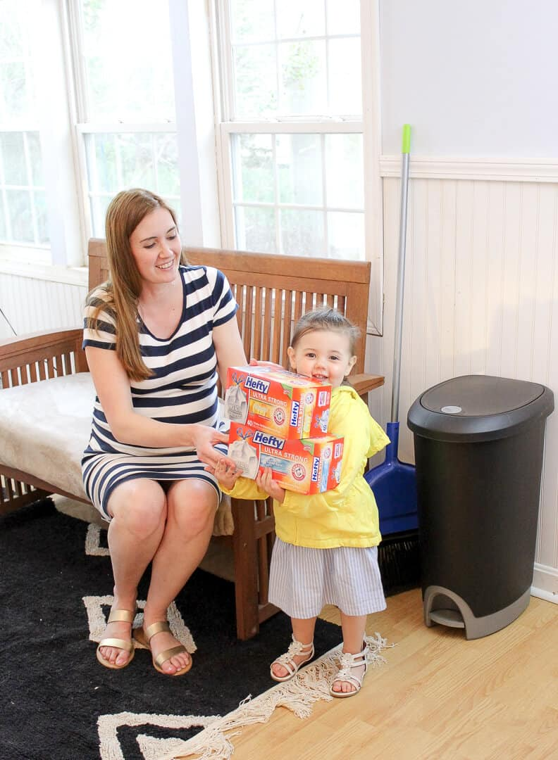 Mother and daughter hold boxes of trash bags from hefty.