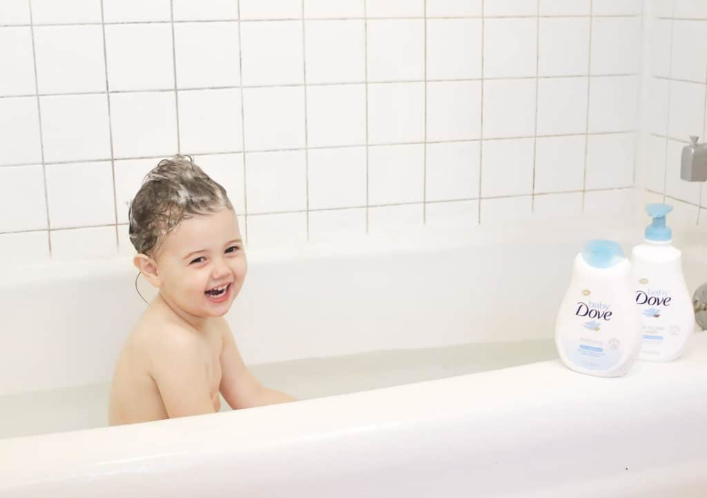 Baby Dove skin care products sit on side of tub with toddler in bath.