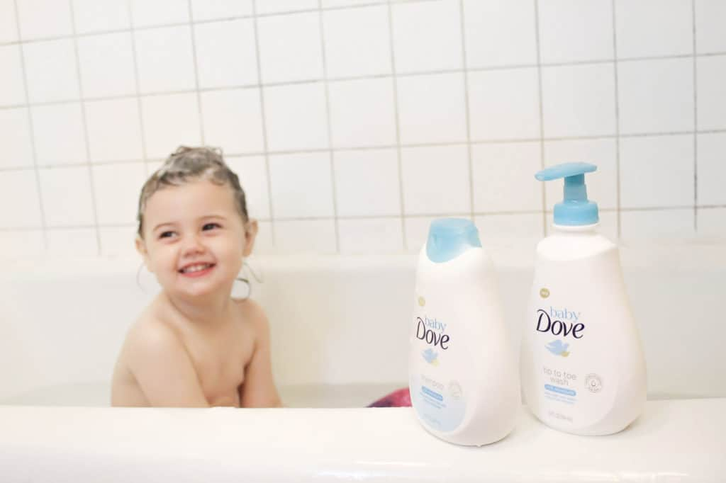 Toddler girl sits in tub with soapy hair.