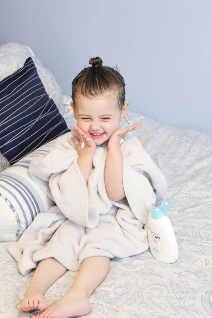 Toddler girl in bathrobe sits on bed.