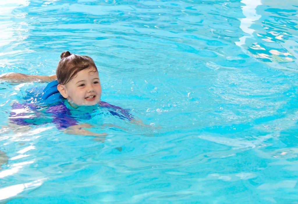 Toddler girl swims in pool.