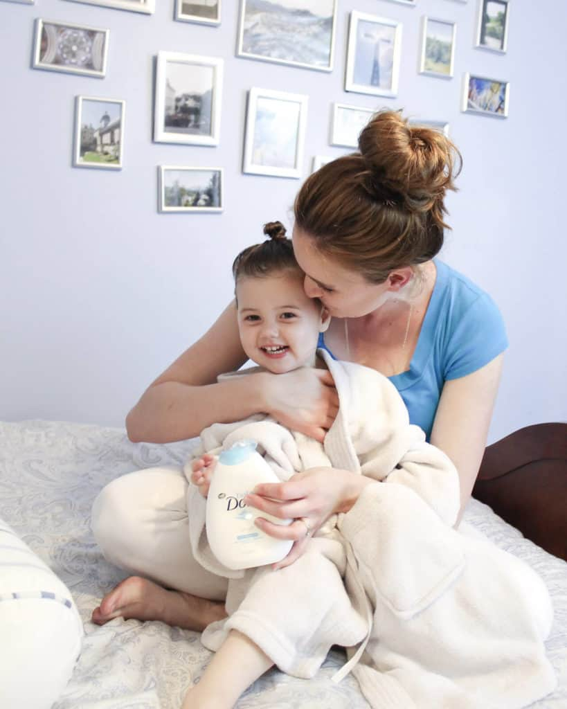 Mother and daughter sit on bed after bath time.